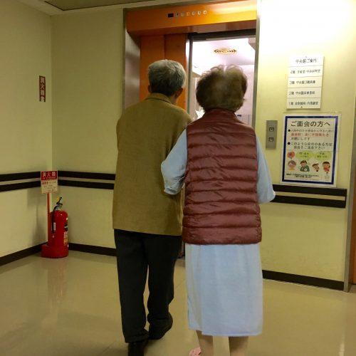 手術室へ向かう母に付き添う父。